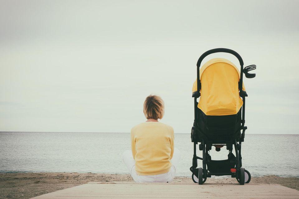 Mutter sitzt neben einem Kinderwagen und schaut aufs Meer