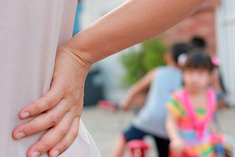 Frau schaut auf Kinder und stemmt die Hand in die Hüfte