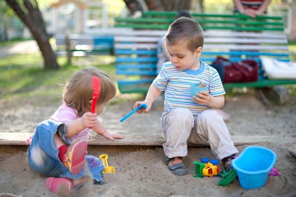 Kinder spielen im Sandkasten zusammen