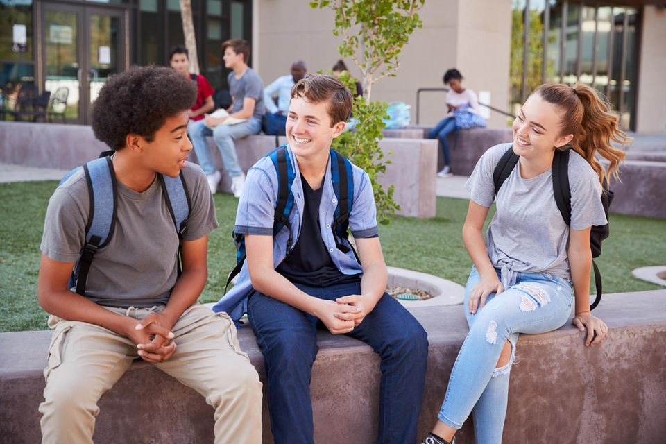 Jugendliche quatschen vor der Schule