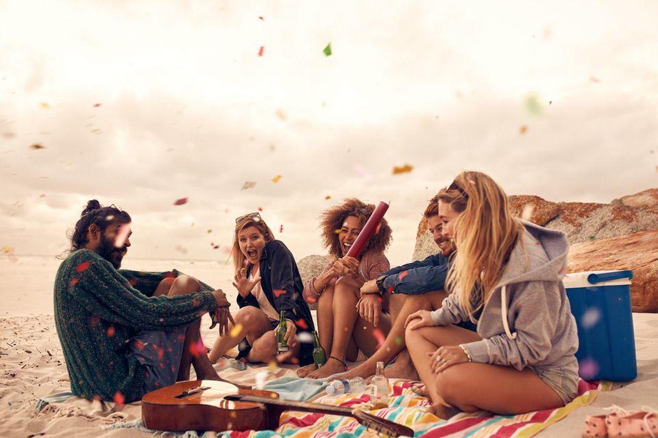 Freunde feiern am Strand zusammen