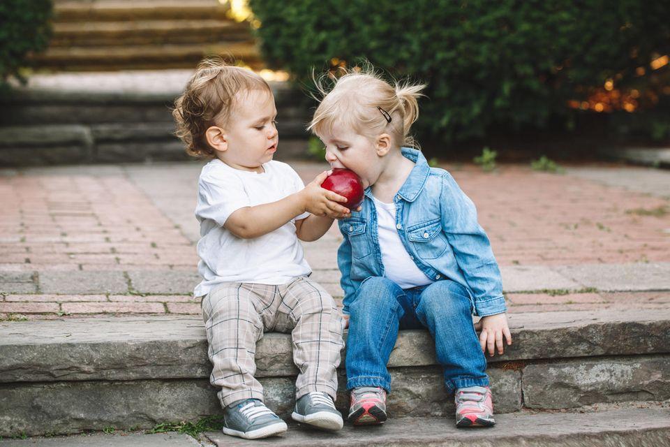 Kleinkinder teilen sich einen Apfel zum Essen