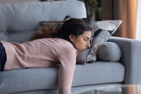 Mutter liegt müde auf der Couch