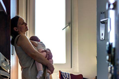 Mutter hat ihr Baby auf dem Arm und lehnt müde in der Küche