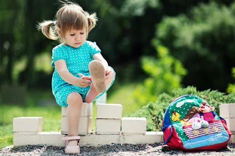 Stickertrick für Kinderschuhe: Mädchen zieht Schuhe an