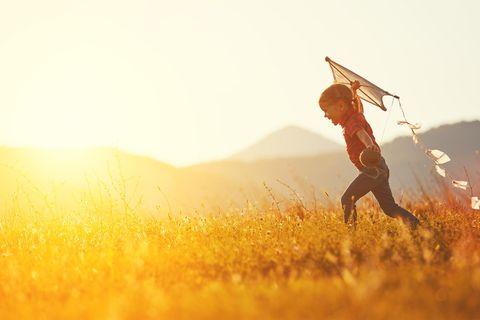 Mädchen lässt einen Drachen fliegen im Sonnenuntergang