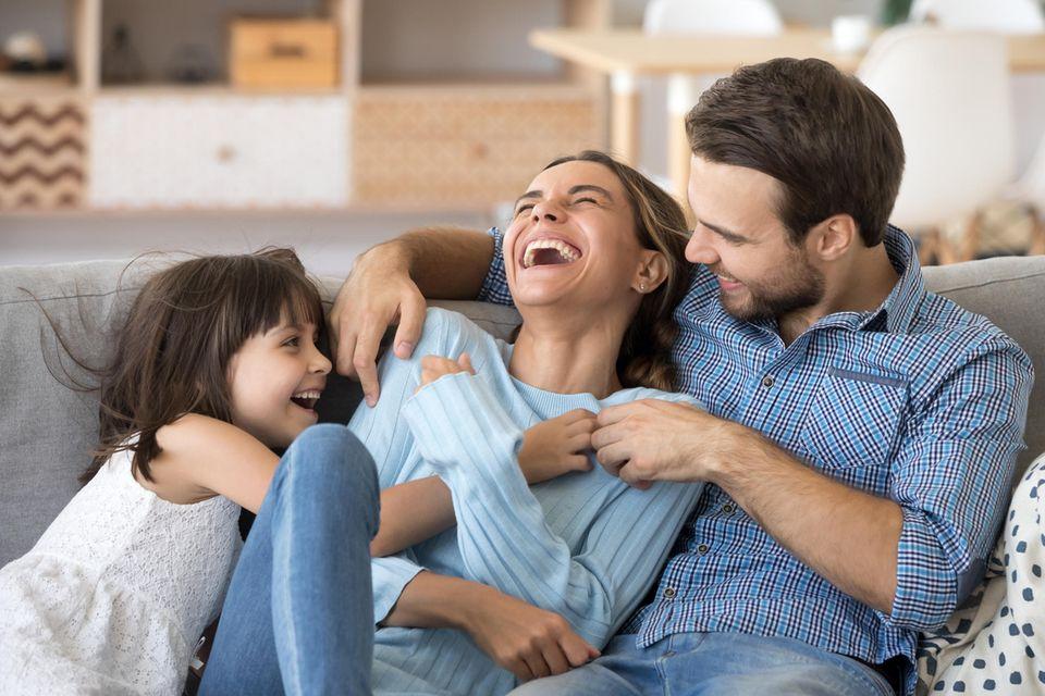 Familie lacht gemeinsam auf dem Sofa