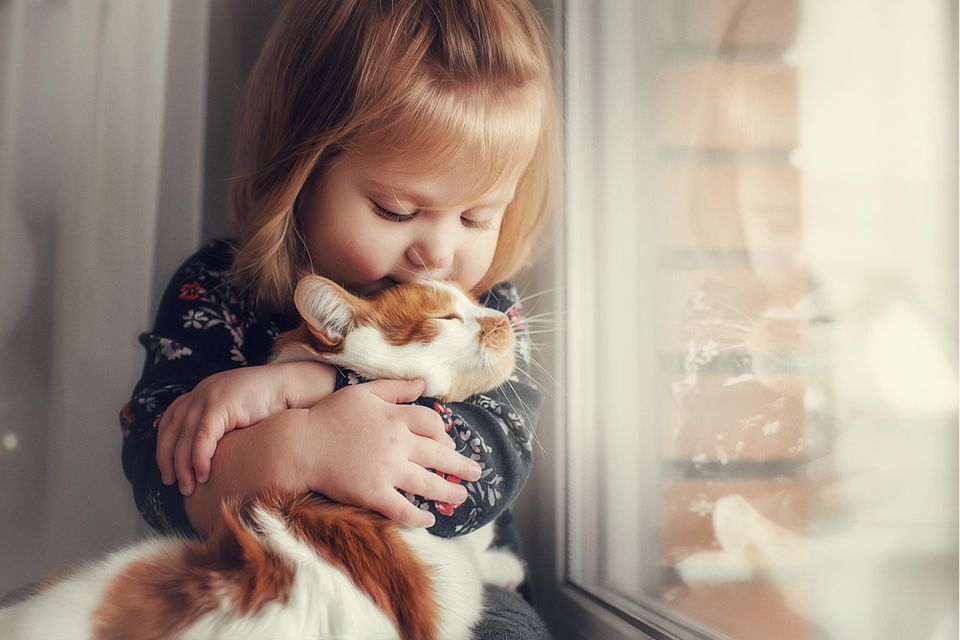 Mädchen kuschelt mit der Katze