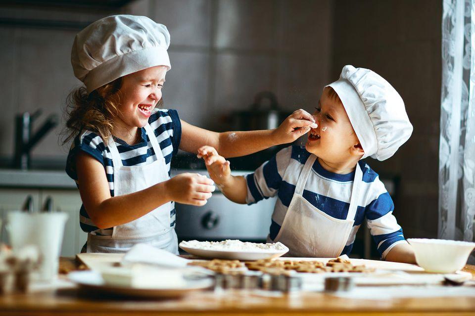 Zwei Kinder backen Kuchen