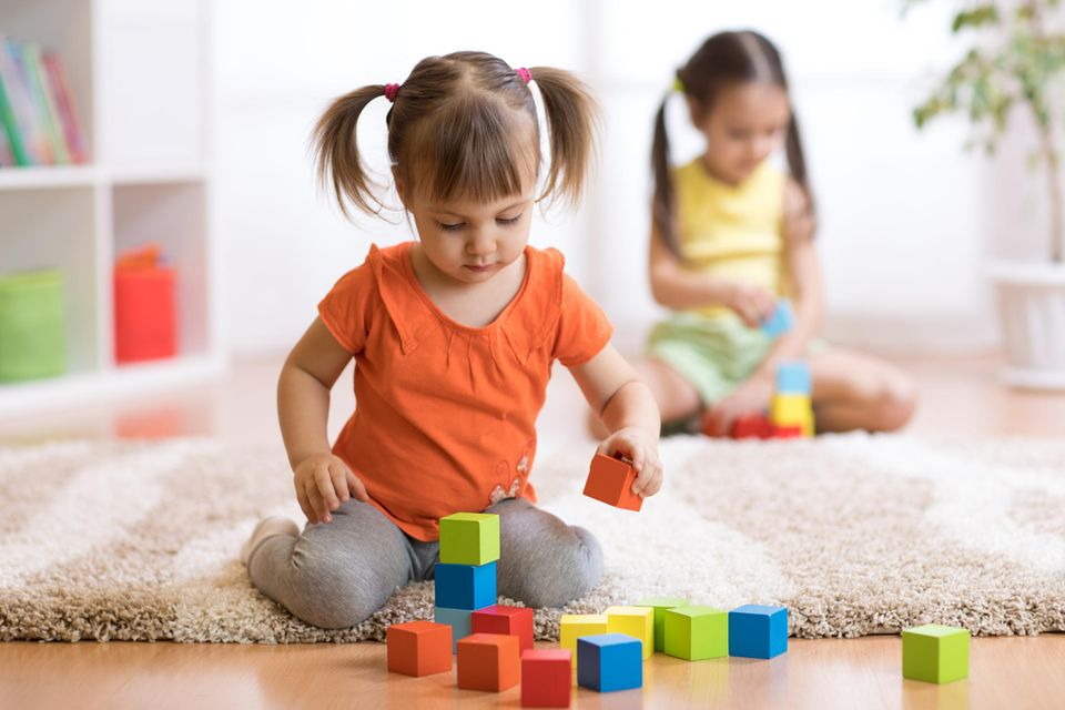 Mädchen spielt mit Bauklötzen