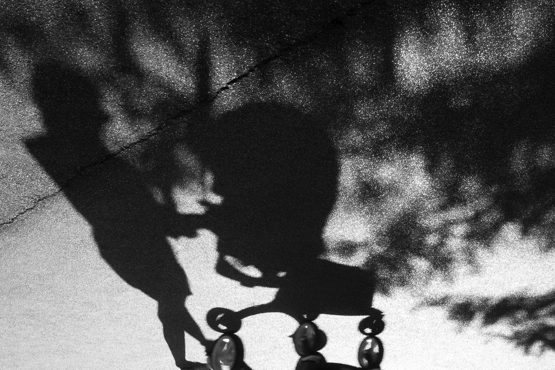 Schatten einer Mutter mit Kinderwagen