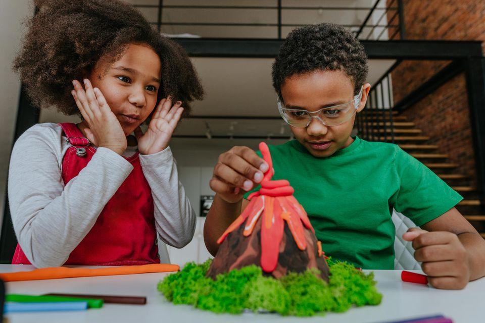 Junge und Mädchen basteln gemeinsam Vulkan