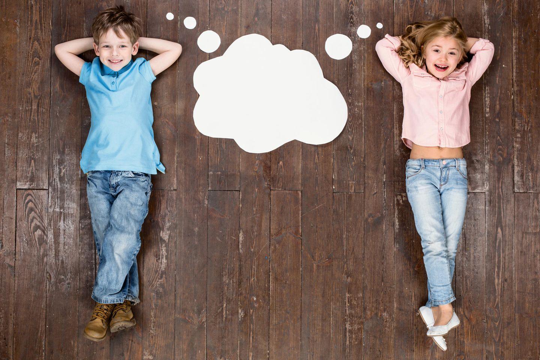 Zwei Kinder liegen auf dem Boden, zwischen ihnen eine Denkblase