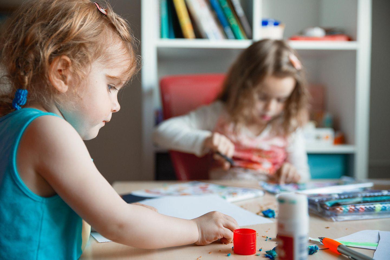 Zwei kleine Mädchen sitzen am Tisch und basteln