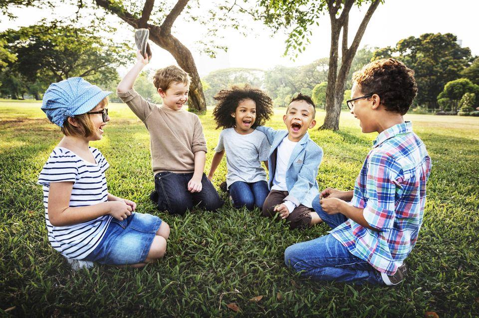 Kinder sitzen in einem Kreis auf dem Rasen und spielen
