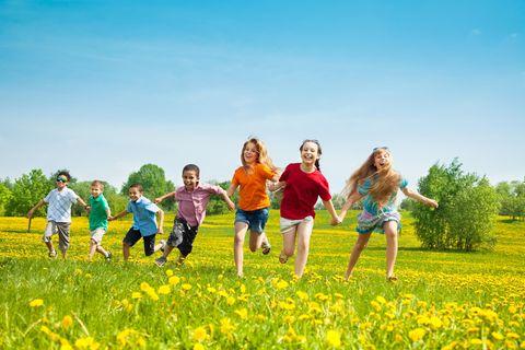 Kinder laufen gemeinsam draußen über eine Wiese