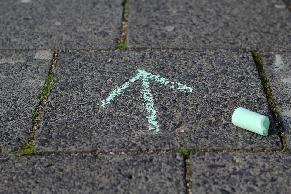 Hellgrüner Kreidepfeil auf dem Boden