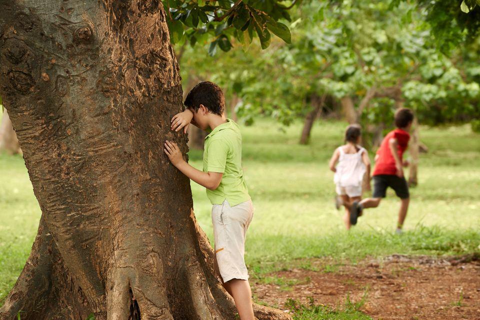 Kinder spielen draußen zwischen Bäumen Verstecken