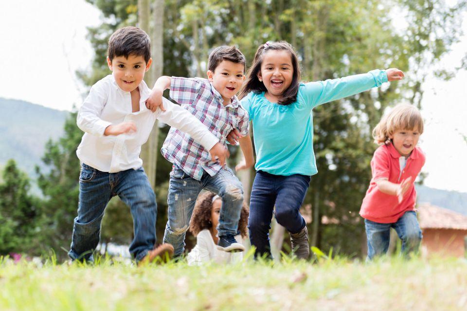 Gruppe von Kindern spielt draußen auf einer Wiese