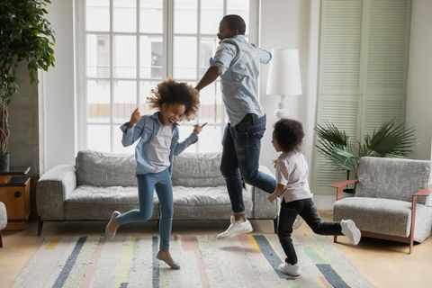 Vater und zwei Kinder tanzen durchs Wohnzimmer