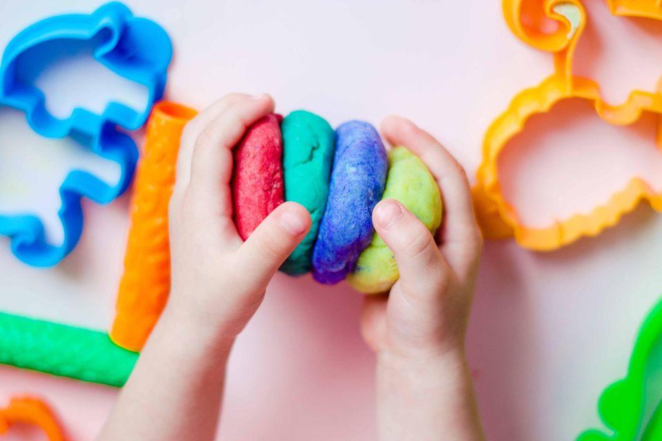 Kind hält bunte Knete in den Händen
