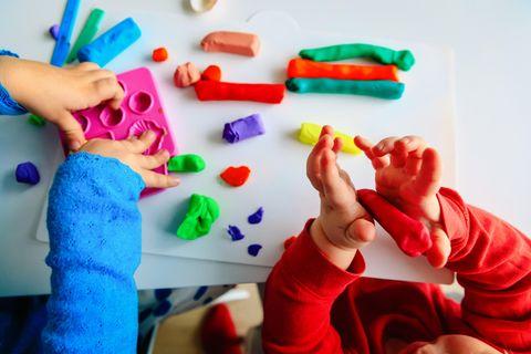 Zwei Kinder spielen mit bunter Knete
