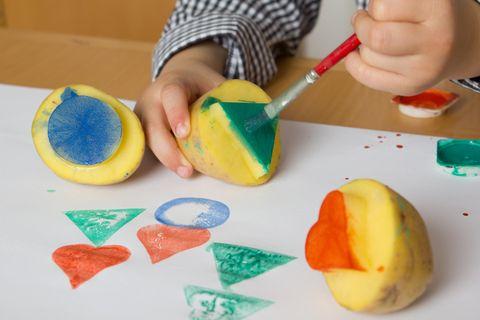 Kind bemalt Kartoffeln für Kartoffeldruck
