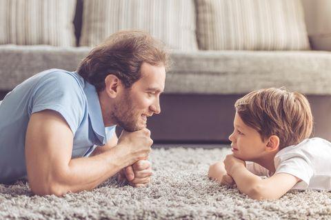 Vater und Sohn liegen auf dem Teppich und sehen sich an