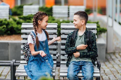 Junge und Mädchen unterhalten sich auf einer Bank