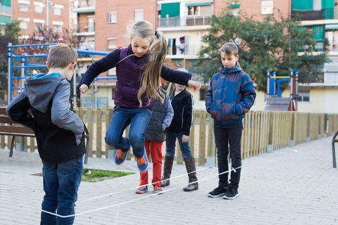 Kinder spielen draußen Gummitwist