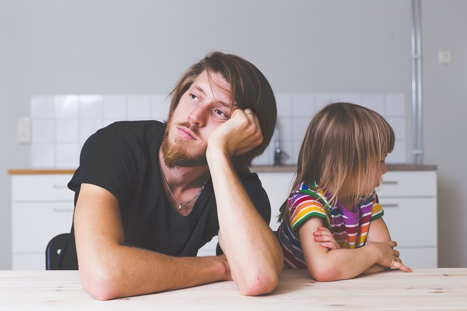 Vater und Tochter am Küchentisch schauen in verschiedene Richtungen