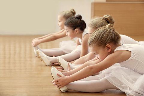 Kleine Ballerinas dehnen sich auf dem Fußboden