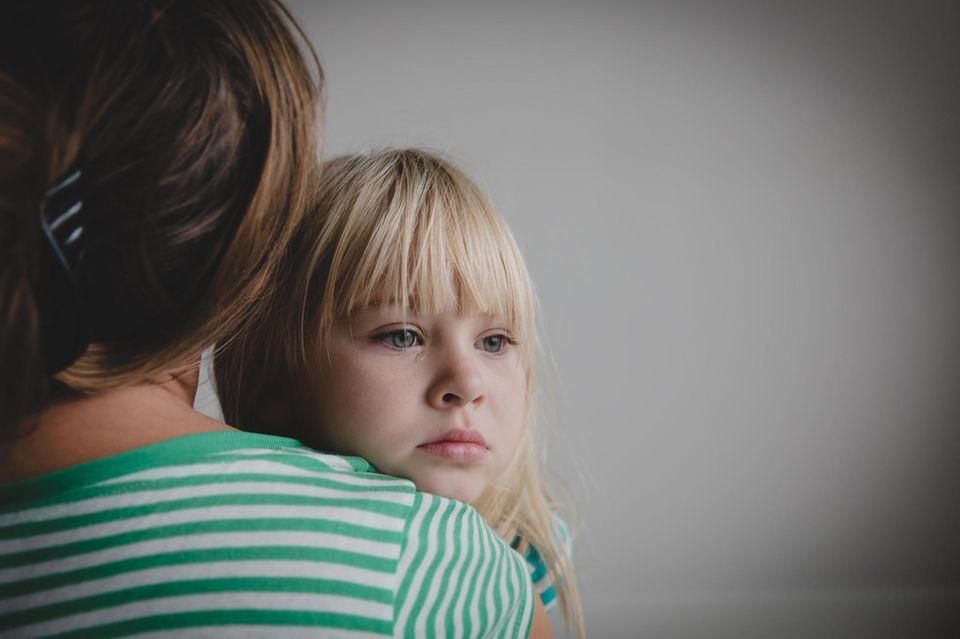 Trauriges Kind auf dem Arm der Mutter