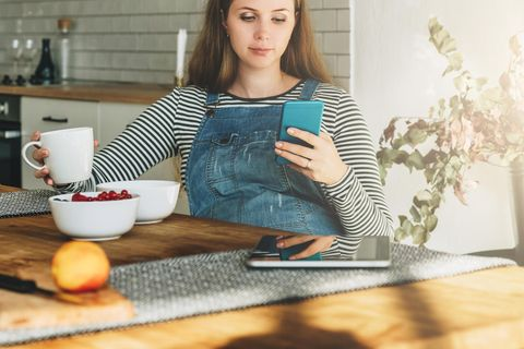 Schwangere sitzt am Küchentisch und schaut auf ihr Smartphone