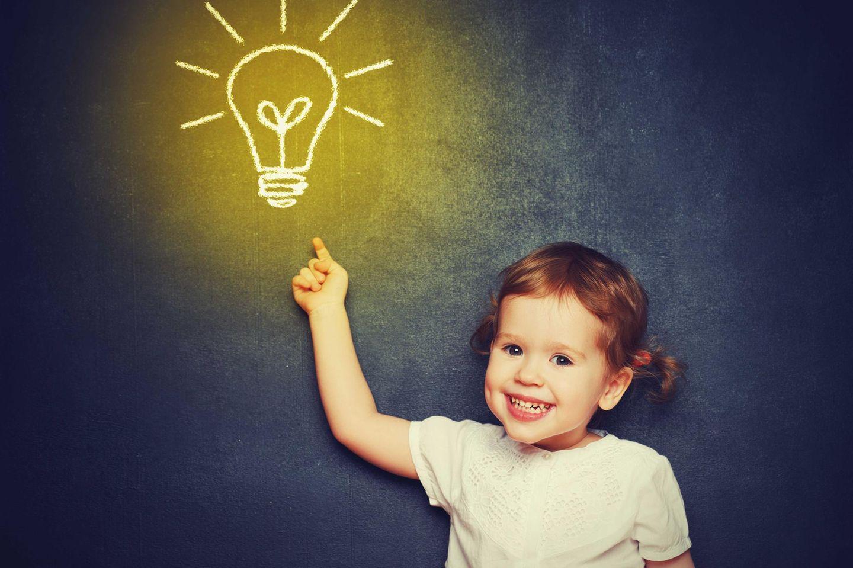 Kind zeigt auf eine symbolische Glühbirne