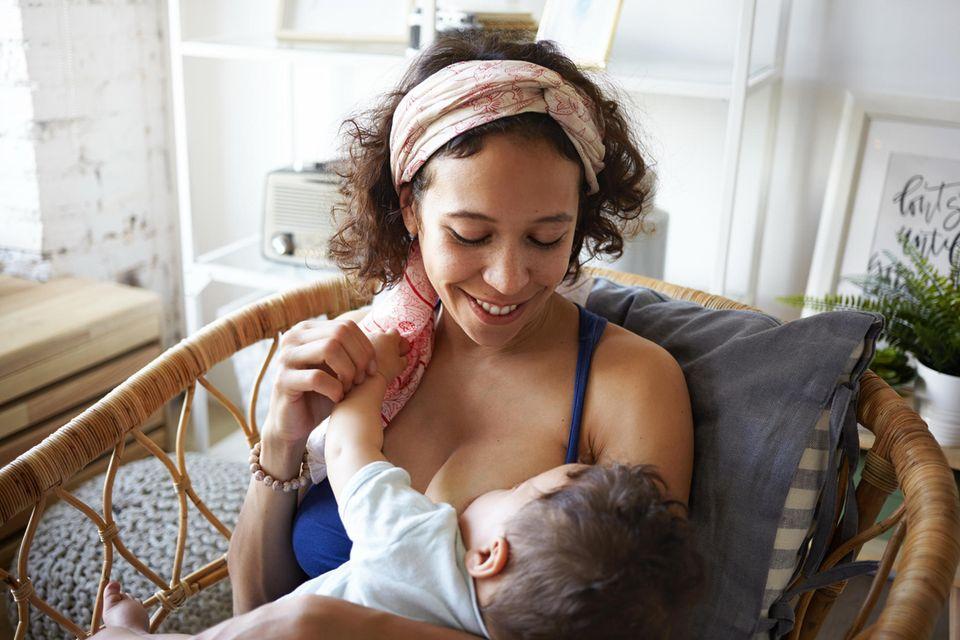Eine Mutter lächelt und schaut ihr Baby an während sie es stillt
