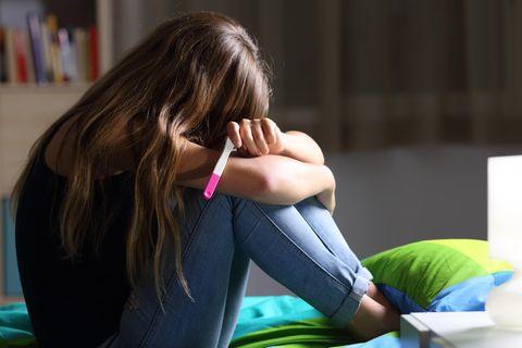 Junge Frau mit Schwangerschaftstest hält traurig den Kopf gesenkt.