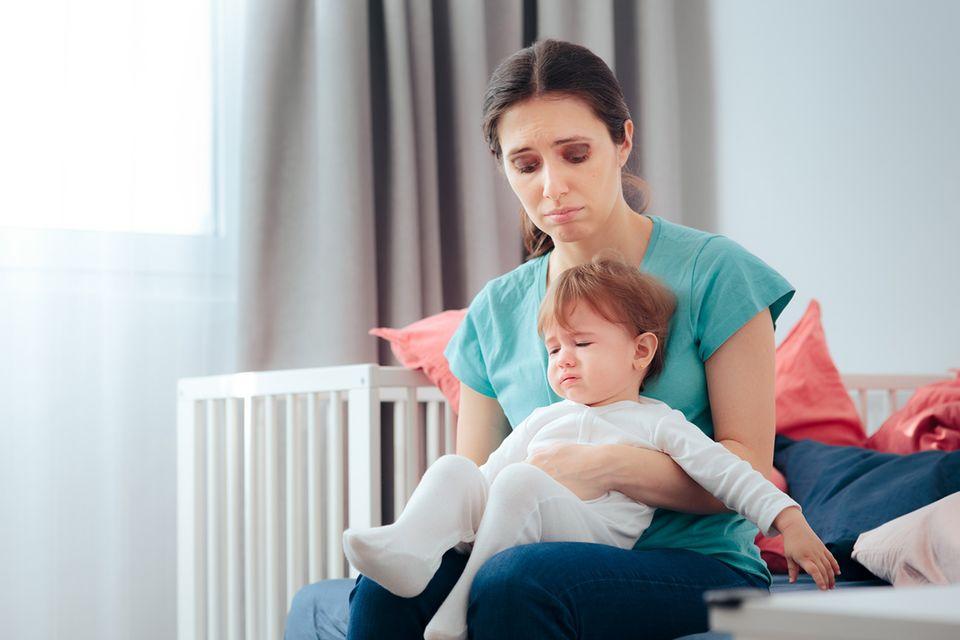 Traurige Mutter hat ihr Kind auf dem Schoß