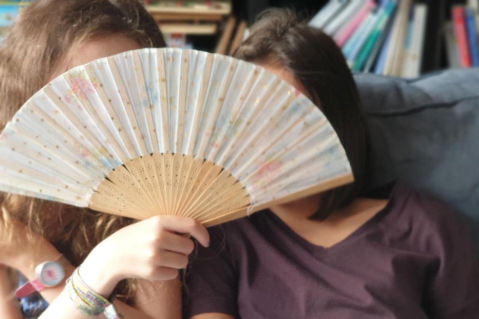 Zwei Mädchen mit Fächer vor dem Gesicht