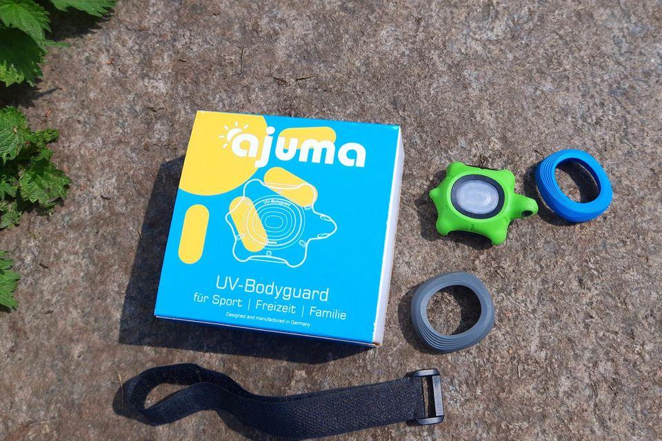 Die Verpackung des ajuma UV-Bodyguards liegt mitsamt Gadget, Cases und Klettverschlussband auf einem Stein im Sonnenschein.