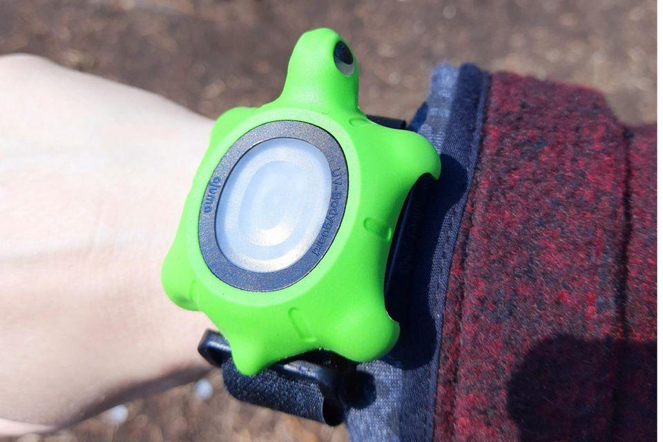 Der UV-Bodyguard im grünen Schildkrötencase am Handgelenk bei Sonnenschein.