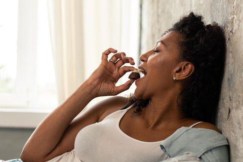 Schwangere liegt entspannt auf dem Bett und isst Schokolade
