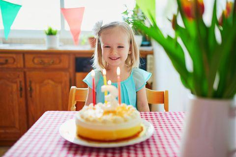Kleines Mädchen sitzt vor einer Geburtstagstorte mit drei Kerzen