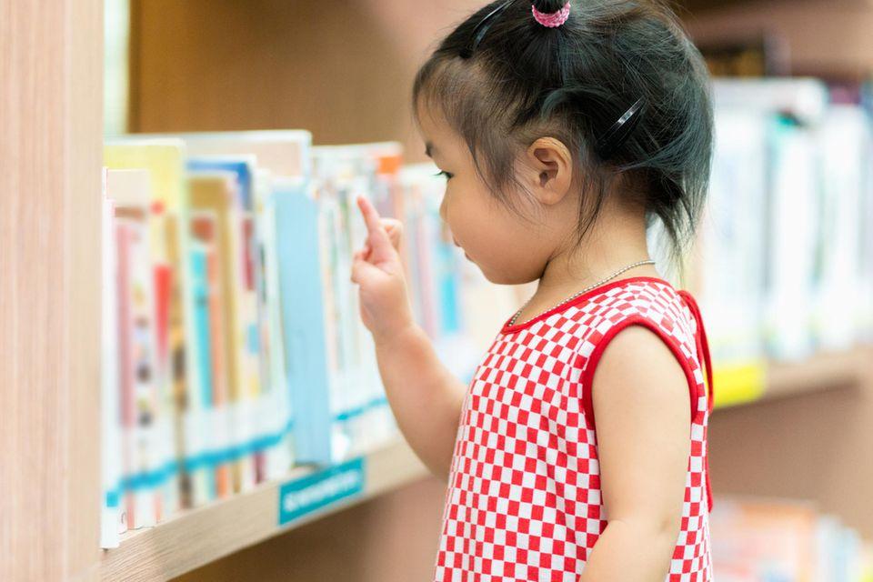 Kleines Mädchen sucht ein Buch in einem Regal