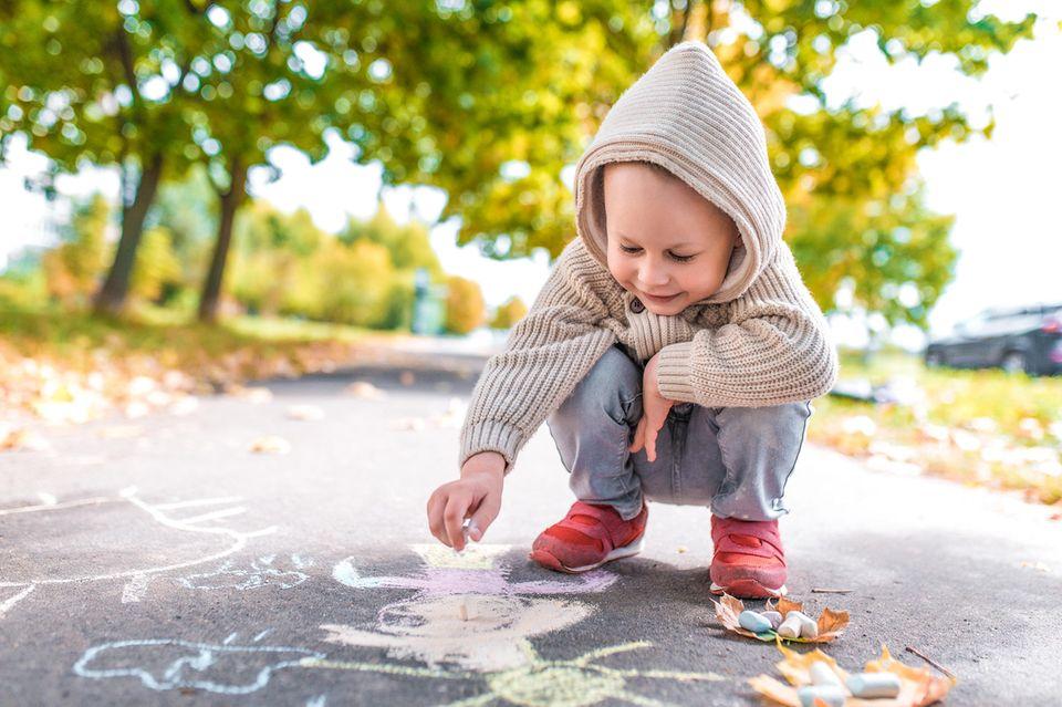 Kleiner Junge mal mit Kreide auf der Straße