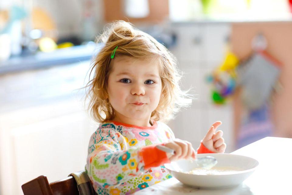 Kleines Mädchen isst Müsli aus einer Schüssel