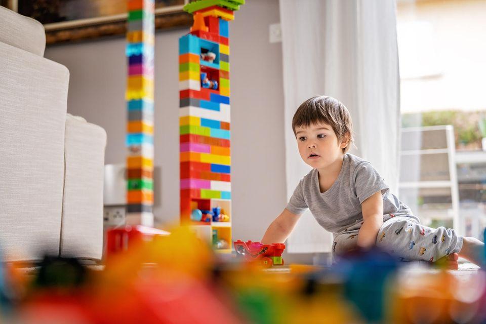 Kleines Kind baut einen hohen Lego-Turm