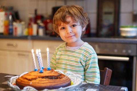 Kleiner Junge feiert seinen vierten Geburtstag mit einem Kuchen und Kerzen