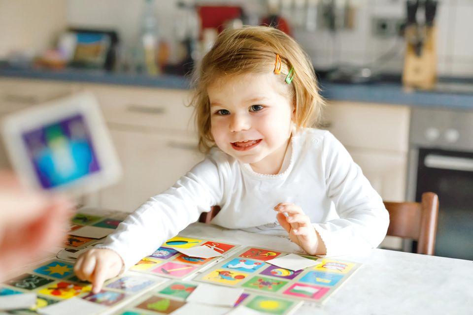 Kleines Mädchen spielt begeistert Memory