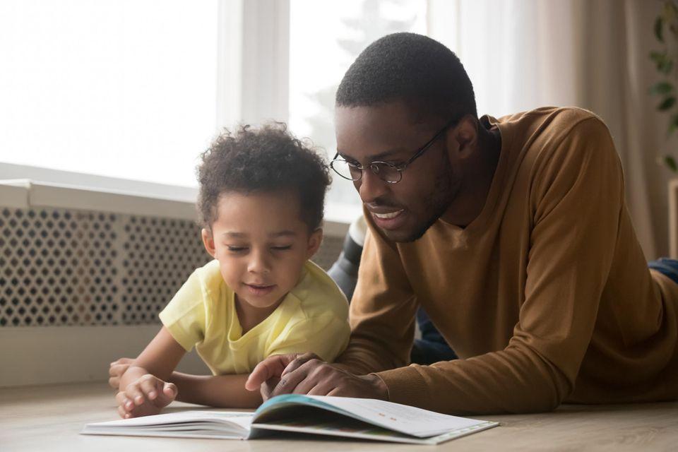 Vater und Sohn lesen zusammen auf dem Boden